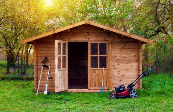 Hovel after work in evening, golden hour. Garden shed (front view) with hoe, string trimmer,  rake and grass-cutter. Gardening tools shed. Garden house on lawn in the sunset. Wooden tool-shed.
