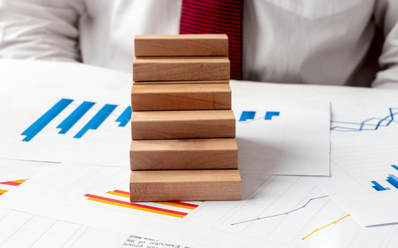 a jenga wooden blocks in the form of a ladder stairs on the graphs of growth and fall on the table. Career ladder concept. Business progress growth concept