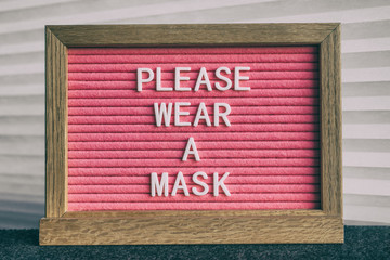 Papiers peints Montagne COVID-19 sign PLEASE WEAR A MASK at grocery store entrance for coronavirus prevention. Message on pink felt letter board. Compulsory measure in businesses for face protection wearing.
