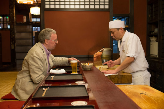 Mature Caucasian man talking with Japanese cook