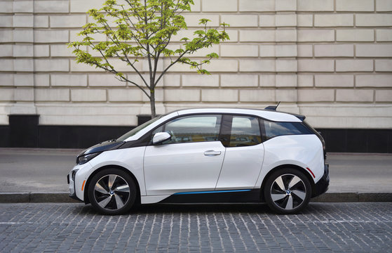 Kiev / Ukraine - 04.22.19: Electric car BMW i3 parked on street near with green tree