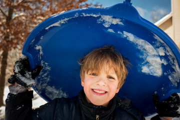 Portrait of a smiling boy carrying a sled, USA