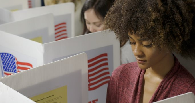 BCU young mixed-race woman, seen from high viewpoint as she casts vote with others at polling station in election