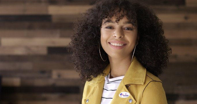 """MCU Young Hispanic woman in yellow leather jacket puts on """"I Voted"""" sticker and smiles. Wooden plank background."""