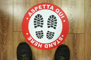 """Footprint sign red color with text """"aspetta qui"""" in italian for  social distance on the floor."""
