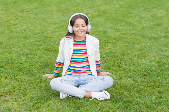 Do not bother me. Listen music while relaxing outdoor. Kid girl enjoy music green grass meadow. Pleasant time. Child headphones listen music. Cool girl headphones listening music. Educational podcast