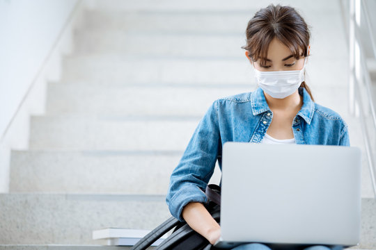 student woman working on laptop at stairs university campus wear mask