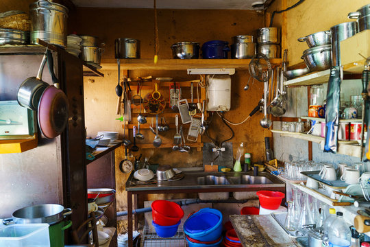 Wide angle view on the kitchen rustic old natural with a lot of dishes plates and utensil sink and boiler in cabin full stacked in the village on farm