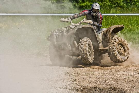 ATV Quad rides fast on big dirt and makes splashes of dirty water, quad racing,  ATV 4x4.  ATV rider.