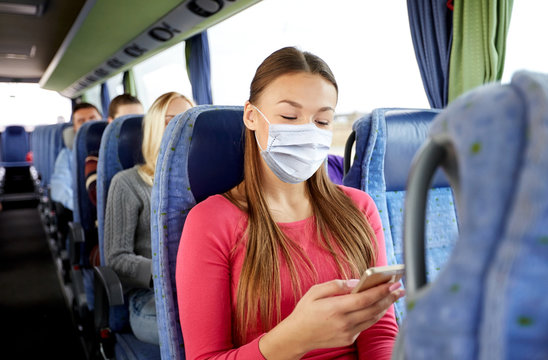 transport, tourism, road trip and people concept - young woman wearing face protective medical mask for protection from virus disease sitting in travel bus with smartphone