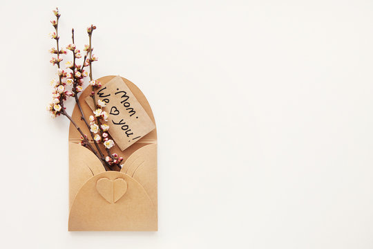Greeting card with text Mom We love you! in craft envelope with heart and bouquet of spring branches and flowers. International Mother's day, birthday, eco concept. Minimalism