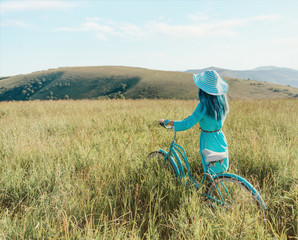 Unrecognizable romantic girl walking with bicycle in summer meadow.