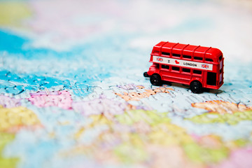 Travel and educational concept. Tourist attractions and souvenir of London red bus on world map background of puzzles for travelers. Copy space