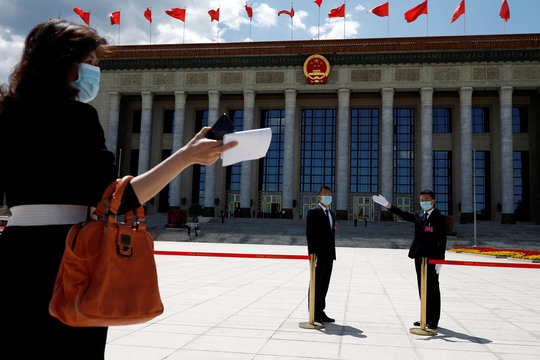 Woman and security personnel are seen before the closing session of CPPCC in Beijing