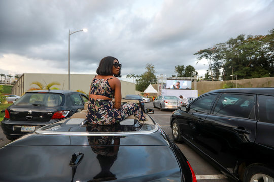"""A woman sits on a car to watch """"Living in bondage"""" movie at a drive-in cinema, following the relaxation of lockdown, amid the coronavirus disease (COVID-19) outbreak in Abuja"""