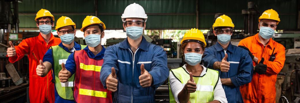 Group of Worker wearing face shield or disposable face mask work in factory to help prevent and fight Coronavirus(Covid-19) or Air dust pollution together wide banner.