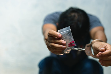 Drug dealer under arrest confined with handcuffs and hands, sale of drugs is punishable by law.