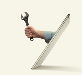 Poster Montagne The human hand with black wrench stick out of a digital tablet screen. Concept of technical support.