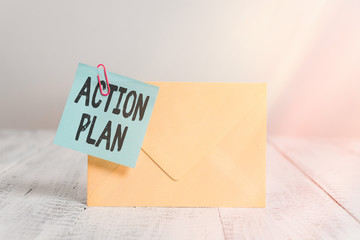 Text sign showing Action Plan. Business photo text detailed plan outlining actions needed to reach goals or vision Standing rectangular colored envelope sticky note clip wooden background