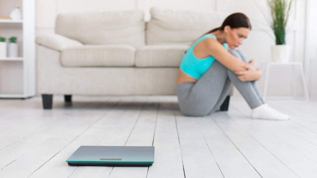 Frustrated Woman Sitting Near Weight Scales At Home, Panorama