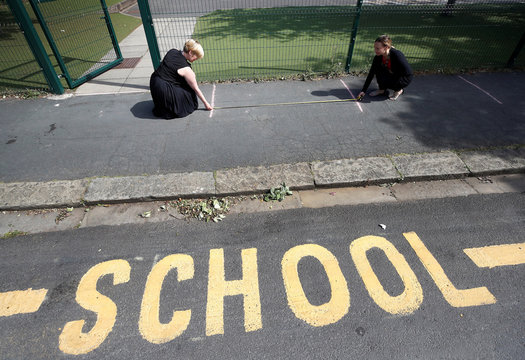 Head teacher Polly Goodson and Deputy Head Claire Cowgill measure out social distancing lines at the entrance to St Anne's CE primary school as the spread of the coronavirus disease (COVID-19) continues in Sale Britain