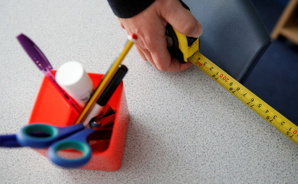 A member of staff uses a tape measure to check desks are correctly spaced for social distancing inside St Anne's CE primary school as the spread of the coronavirus disease (COVID-19) continues in Sale