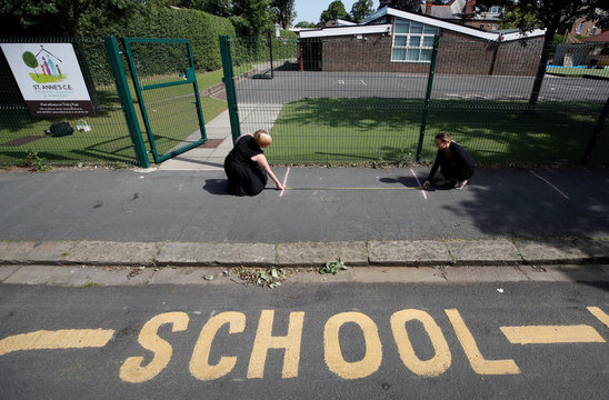 Head teacher Polly Goodson and Deputy Head Claire Cowgill measure out social distancing lines at the entrance to St Anne's CE primary school as the spread of the coronavirus disease (COVID-19) continues in Sale