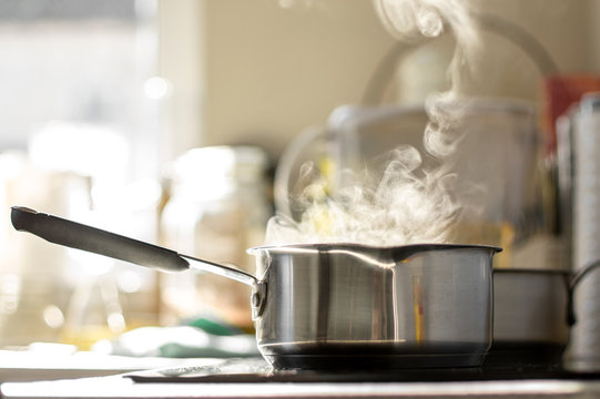 Boiling water with a steam in a pot on a electric stove in the kitchen