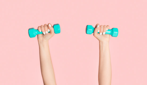 Young girl lifting dumbbells on pink background, closeup of hands. Panorama