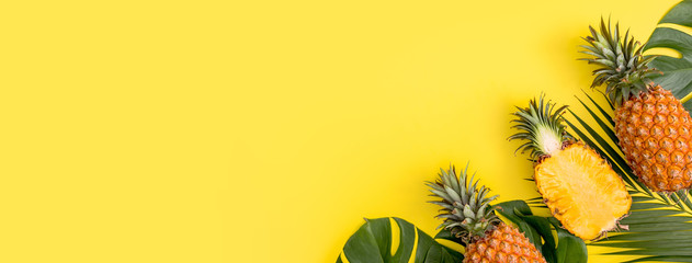 Canvas Prints Palm tree Beautiful pineapple on tropical palm monstera leaves isolated on bright pastel orange yellow background, top view, flat lay, overhead above summer fruit.