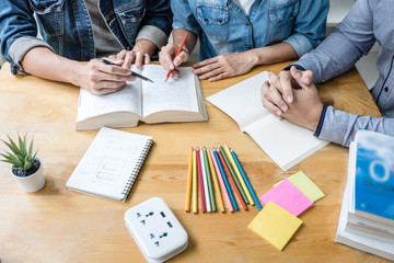 High school tutor or college student group sitting at desk in library studying and reading, doing...