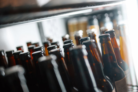 Bottles of beer in the fridge of a bar. Different focus