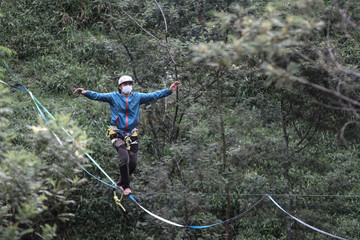 A man wearing a protective face masks practices highlining at a Merapi mountain slope forest amid the coronavirus disease (COVID-19) outbreak in Klaten