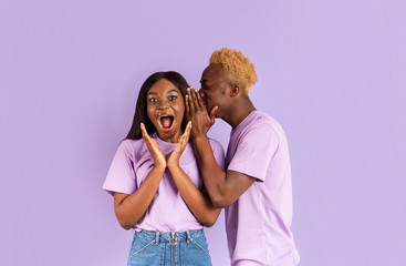 Handsome black man whispering secret or interesting gossip to woman's ear on color background