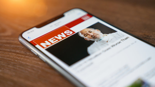 Close up of businessman reading news or articles in a mobile phone screen app. Hand holding smart device. Mockup website. Newspaper and portal on internet. Displayed news are not reality related.