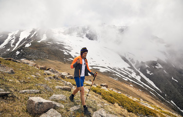 Hiker with trekking poles in the foggy mountains