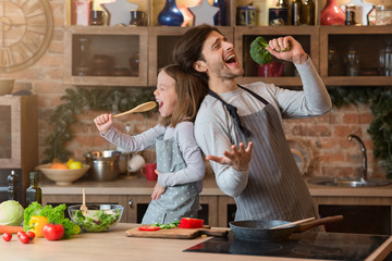 Kitchen Fun. Cheerful dad and his little daughter singing while cooking together