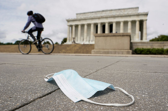 A cyclist passes a discarded face mask in front of the Lincoln Memorial during the coronavirus disease (COVID-19) pandemic in Washington