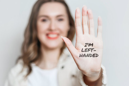 Left-handed girl shows her left hand to the camera and smiles isolated over gray background, celebrating left-handed day, text I'm left-handed on hand
