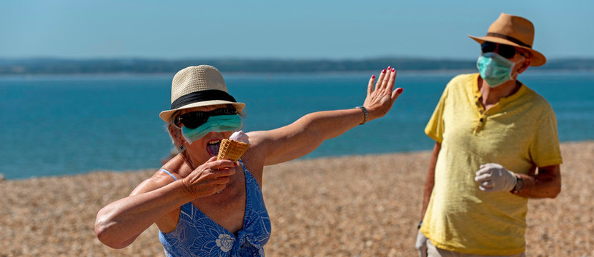 Southsea, Portsmouth, Southern England, UK. May 2020. Woman eating ice cream whilst wearing a mask and rubber protective gloves and social distancing from her husband during the Corvid-19 outbreak.