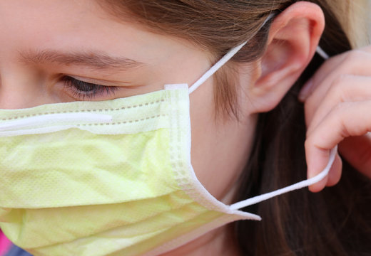child properly wearing surgical mask with elastic behind the ear