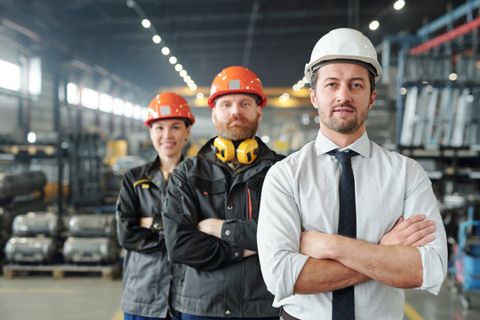 Confident leaders of manufacturing production plant standing with crossed arms in row at factory
