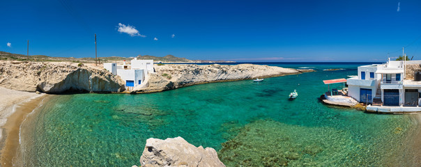 Greece scenic island panorama - small harbor with fishing boats in crystal clear turquoise water, traditishional whitewashed house. MItakas village, Milos island, Greece.