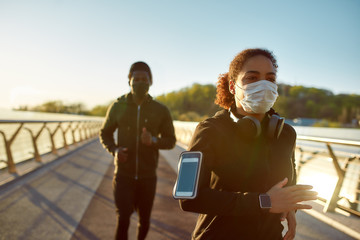 Young african man and woman in medical masks running on the bridge during a pandemic. Sport and...
