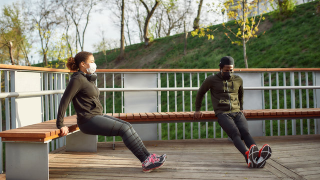 Keeping distance. African couple in protective masks working out in park outdoors. Doing push-ups exercises on bench, training triceps. Social distancing