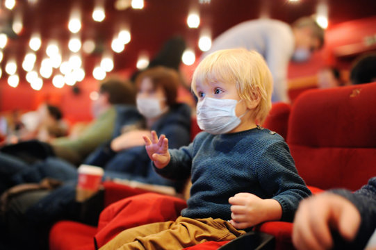 Cute toddler boy wearing face mask watching cartoon movie in the cinema after quarantine. Lifting virus lockdown. Social distancing restrictions remain.
