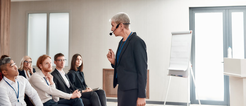 Leadership Lessons. Female speaker in suit with headset giving a talk on corporate business meeting
