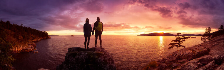 Fototapeten Lachs Fantasy Adventure Composite of a Man and Woman Couple on a Rocky Coast during a colorful dramatic sunset. Background taken from Lighthouse Park, West Vancouver, British Columbia, Canada.