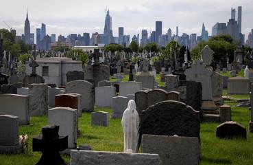Manhattan Skyline beyond graves in Calvary Cemetery during outbreak of the coronavirus disease (COVID-19) in New York