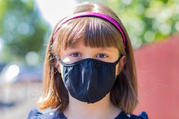 Portrait of a girl wearing her protective facial mask correctly outdoor. Concept of coronavirus.